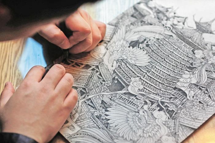 蘭才生在插畫館內繪製以侗寨鼓樓為主題的插畫作品。本組圖片由新華社提供