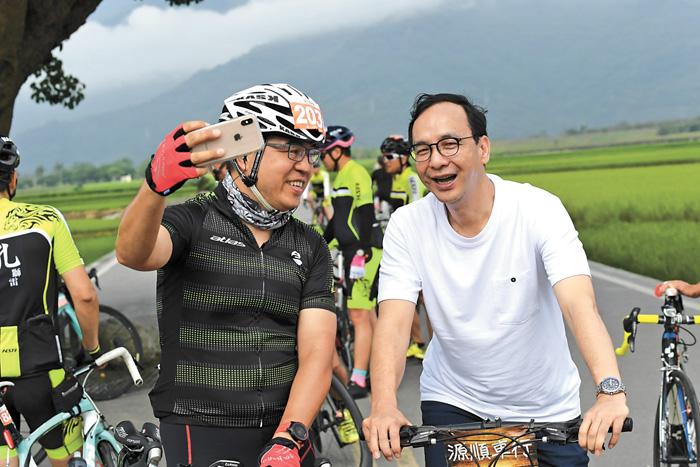 朱立倫(右)來到台東池上鄉騎單車,並與民眾開心合影。中央社