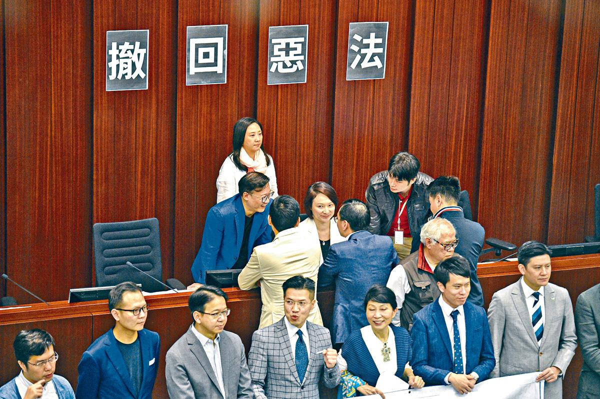 內務委員會會議會前,民主派議員走向主席台抗議,主席李慧琼獲黨友「護駕」。 陳浩元攝