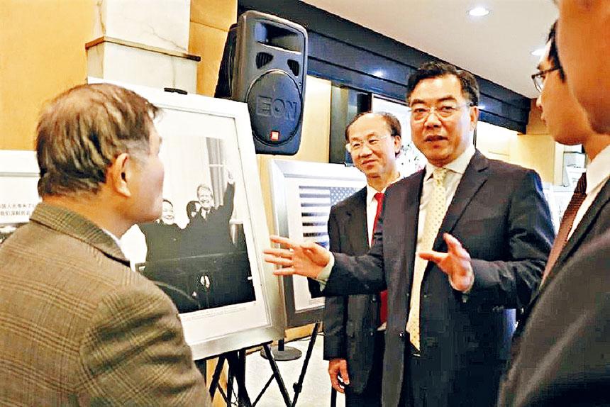 黃屏向僑胞們介紹圖片展中鄧小平和卡特總統的合影。