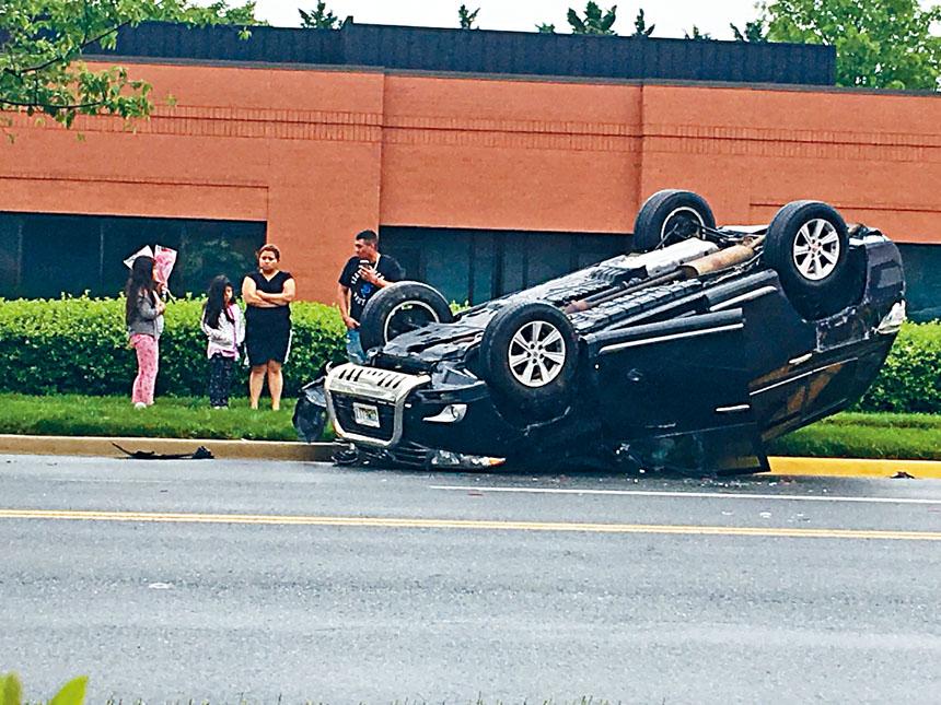 全家四口站在翻倒的車輛旁。