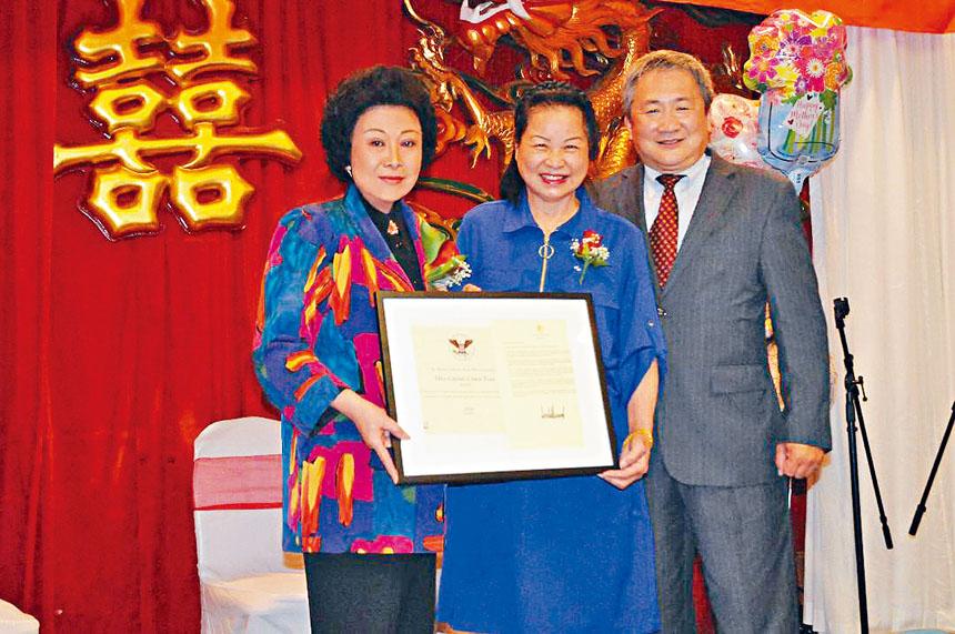 蘇麗凰(左)向陳惠青(中)轉交總統義工獎獎狀與賀信。右為鄭文彬。