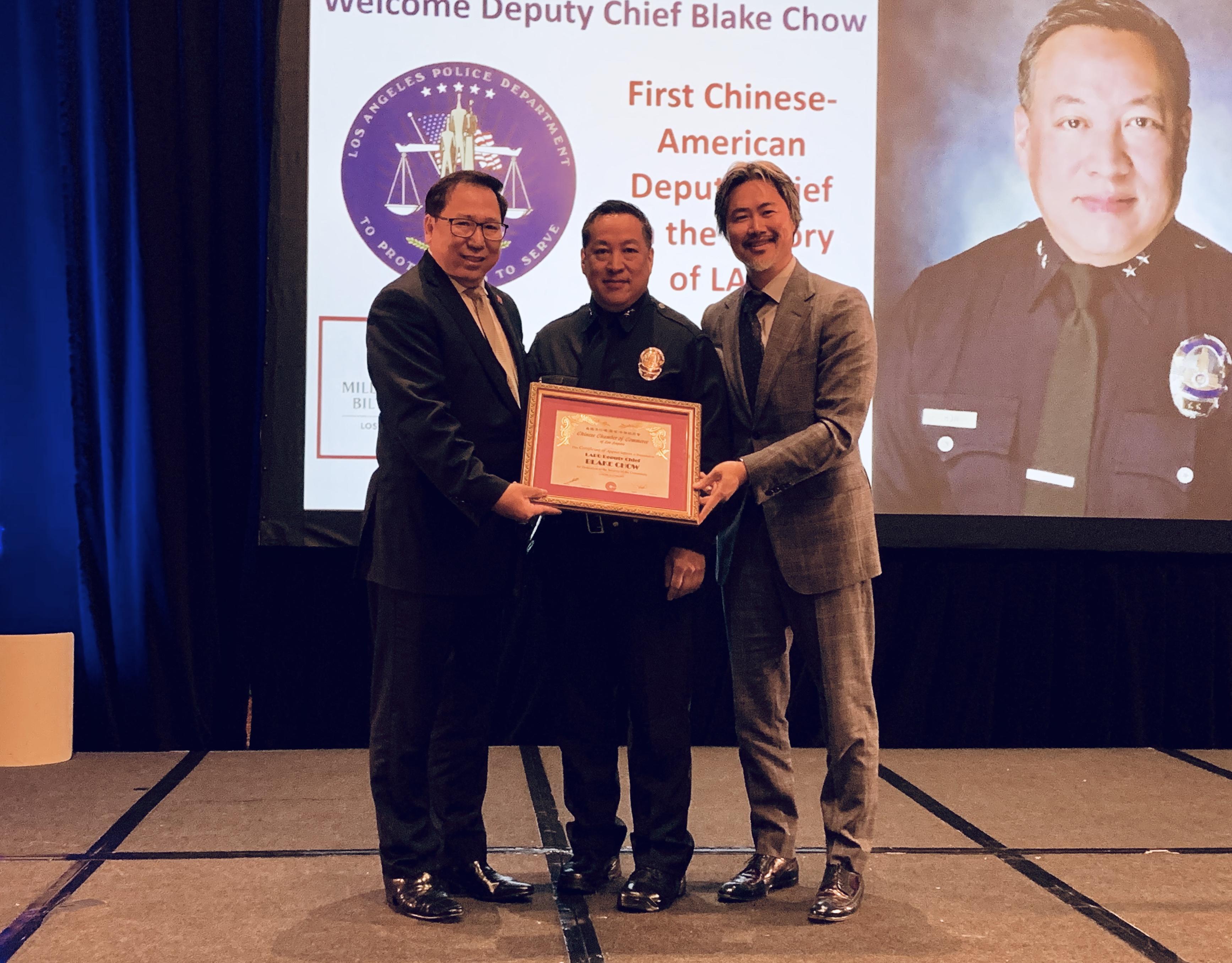 羅省中華總商會主席莊佩源(左)與會長陳嘉汶(右)致贈洛市警局副局長周寶來(中)賀狀。記者黃品瑄攝