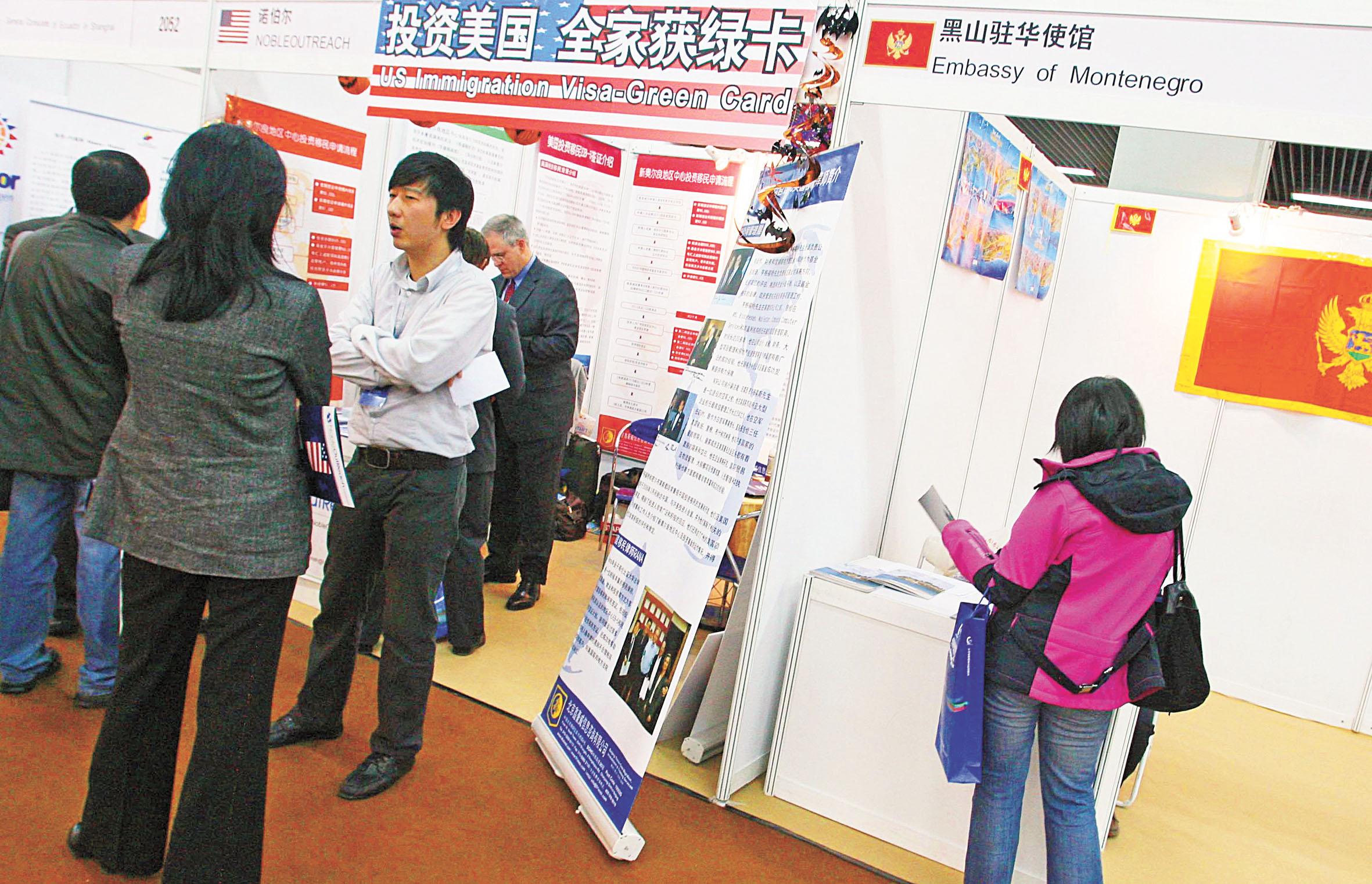 許多中國人通過投資移民入籍美國。圖為中國對外投資合作洽談會展會上,一家投資移民美國的公司展位受到觀眾的追捧,前來詢問的觀眾絡繹不絕,與隔壁的歐洲黑山共和國展位的冷清形成強烈對比。 香港中通社資料圖片