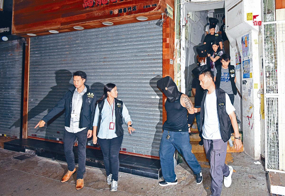 ■探員在旺角花園街樓上釣魚機賭場拘捕一批兌分仔及賭客。丁志雄攝