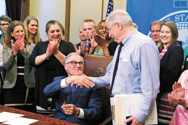 州長英斯利簽署法案,與前州眾院議長索普握手。美聯社