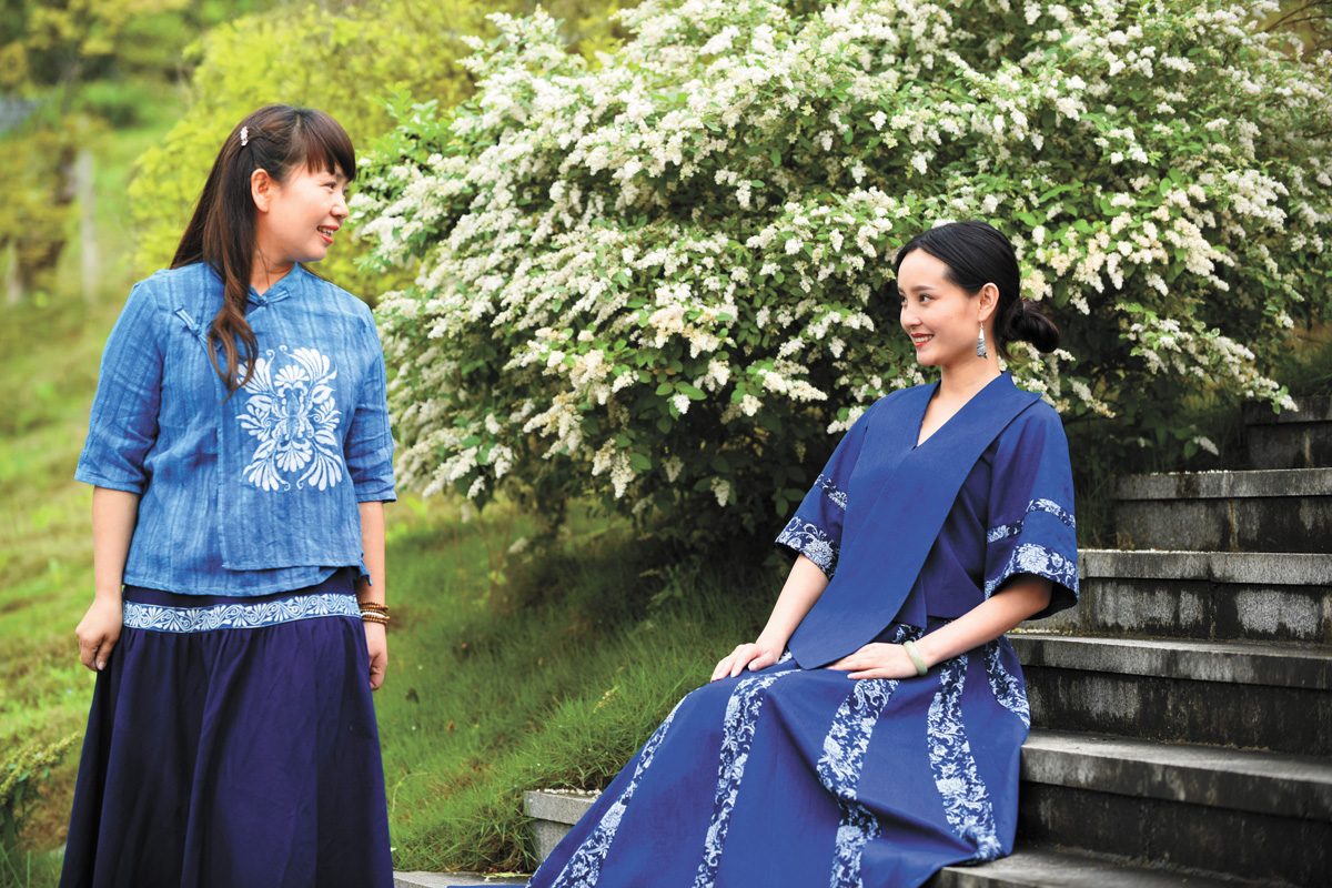 冉光津(右)與教師李宏穿著「楓香染」工藝服飾拍照,然後放到網上進行展示。本組圖片來自新華社
