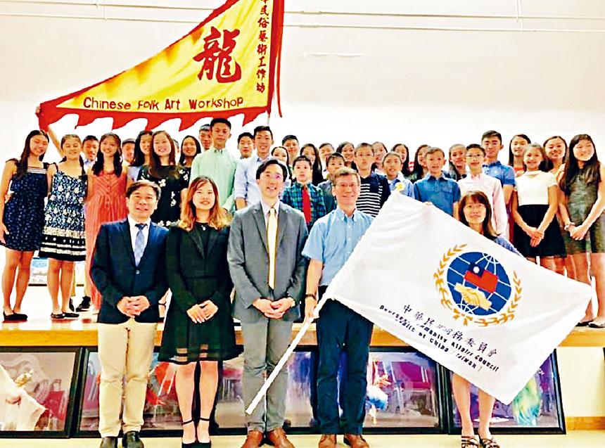 張昆團長從徐佑典處長(前排中)手中接過僑委會會旗。主辦方提供