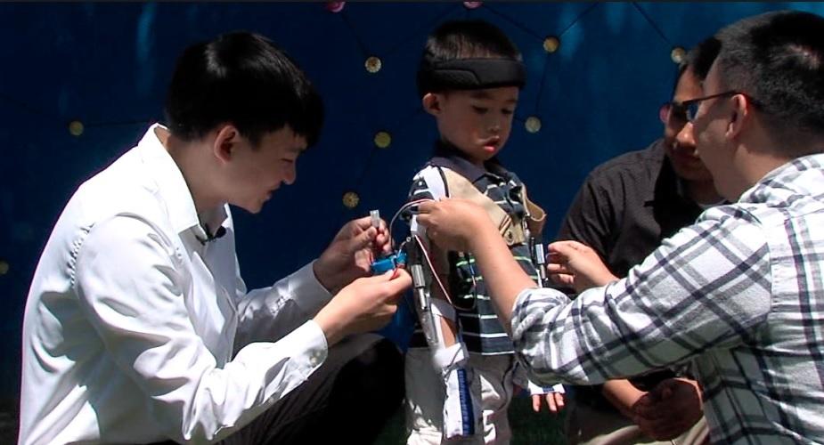 設計輔具的學生細心替馬克斯綁上裝有感應器的矯正支架,戴上裝有感應器的特殊手套,讓馬克斯有如小鋼鐵人一般。abc 10 News