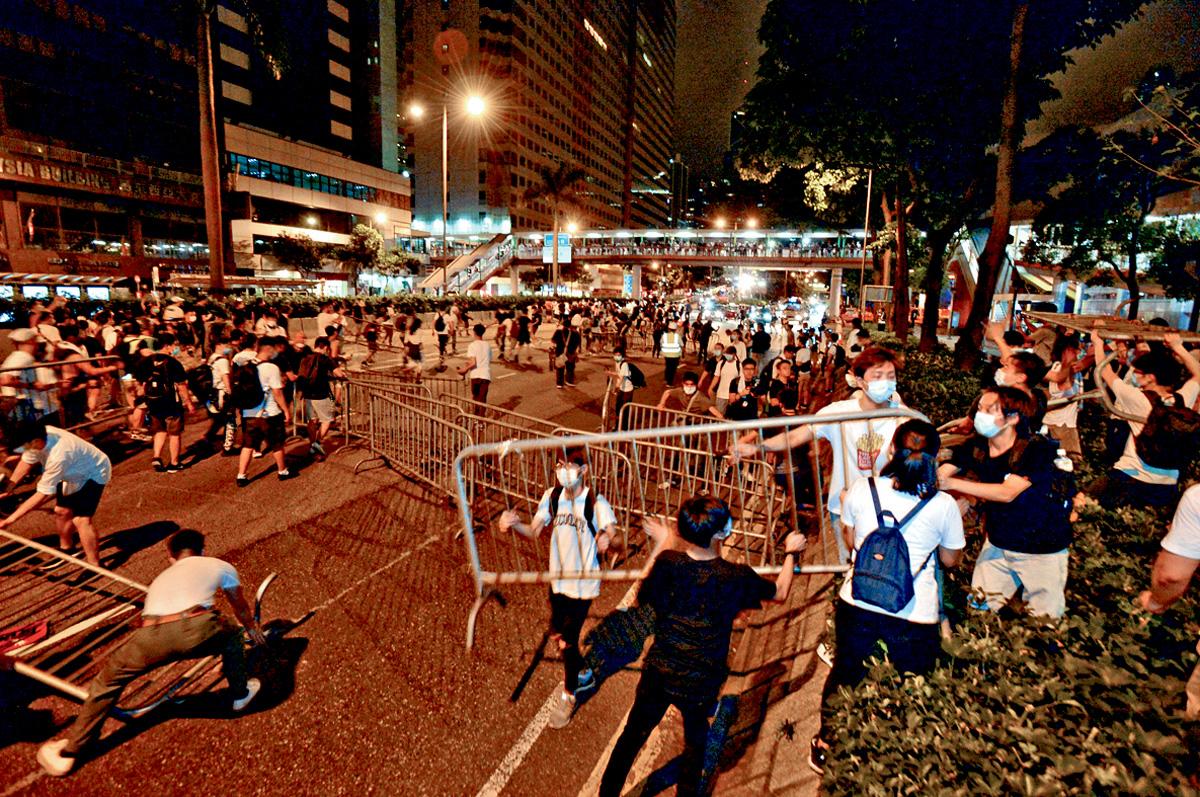 示威者將大量鐵欄抬至告士打道堵路。伍明輝攝