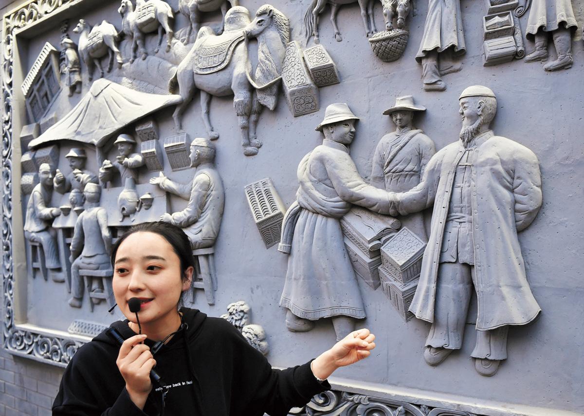 在甘肅省臨夏市八坊十三巷街區,一名導遊在介紹磚雕作品。本組圖片來自新華社