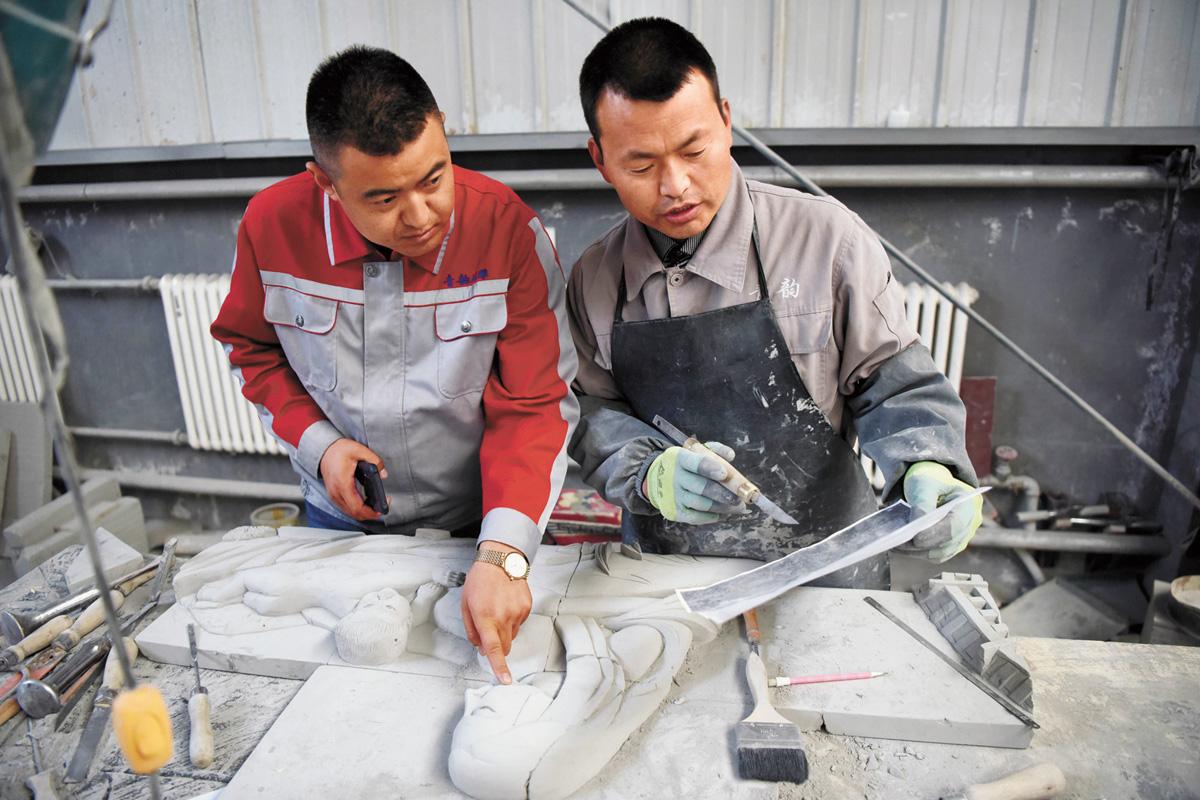兩名工作人員根據需求在一起商討磚雕的製作方案。