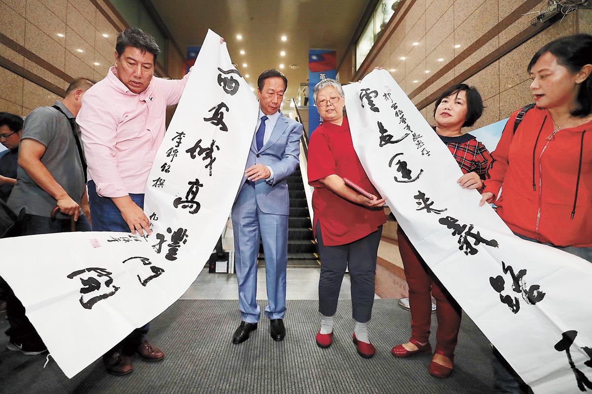 國民黨11日召開總統初選參選人座談會,有支持者送上字聯為郭台銘(右4)加油打氣。中央社
