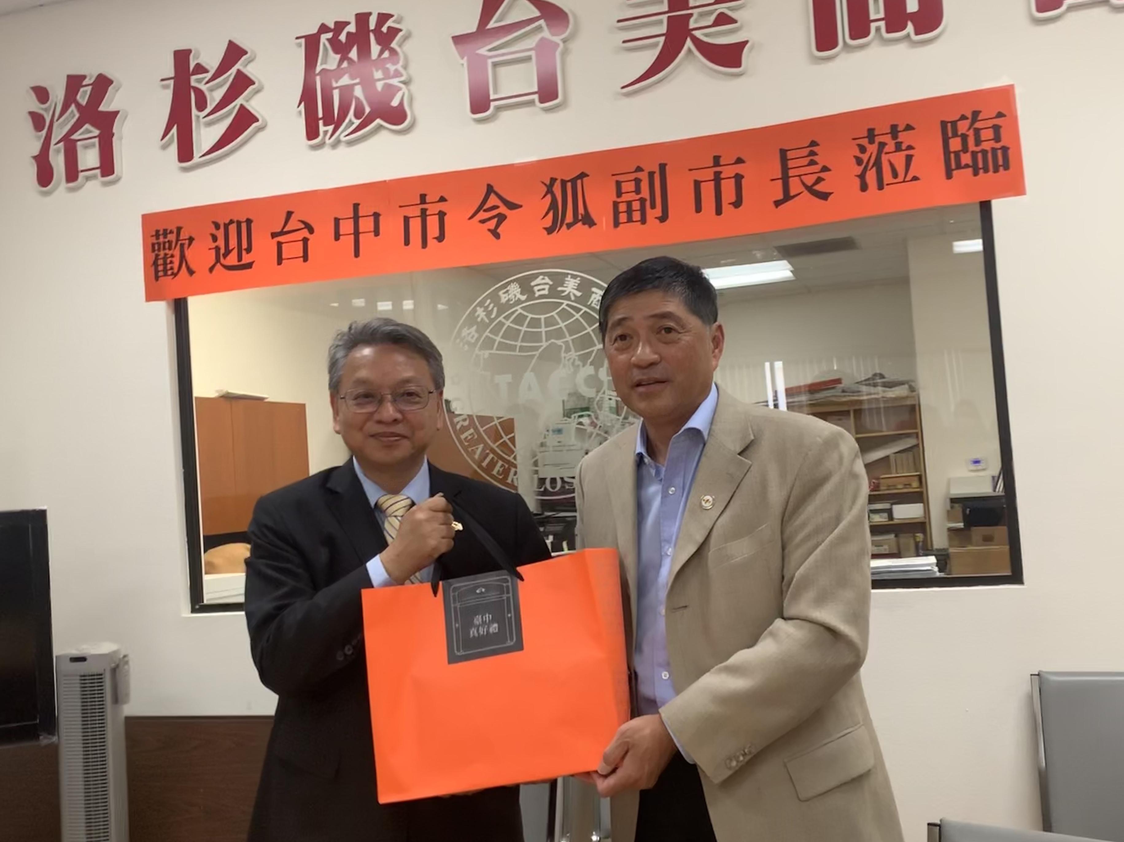 洛杉磯臺美商會會長陳慶恩(右)接受臺中市副市長令狐榮達(左)贈送的禮物。記者楊婷攝