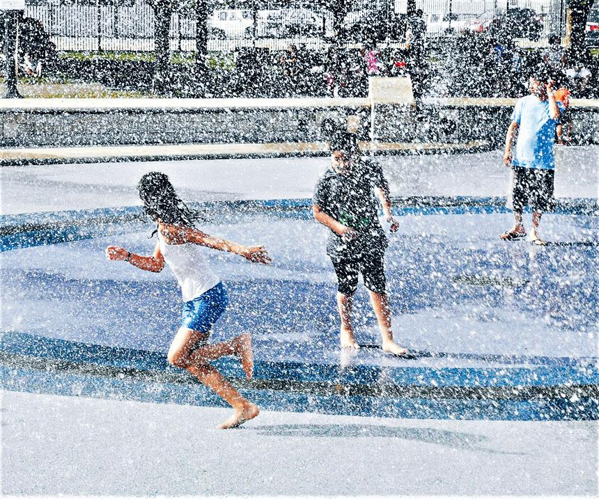 孩童們在東波士頓一公園的噴水池玩耍。李強攝