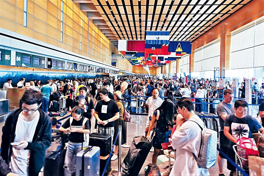 洛根機場獨立日長周末旅客大排長龍。李強攝