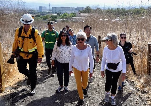 爾灣市長璽雅、副市長郭志明、市議員卡恩與消防員及市民們查看爾灣野草叢生的開放區域。龐可陽攝