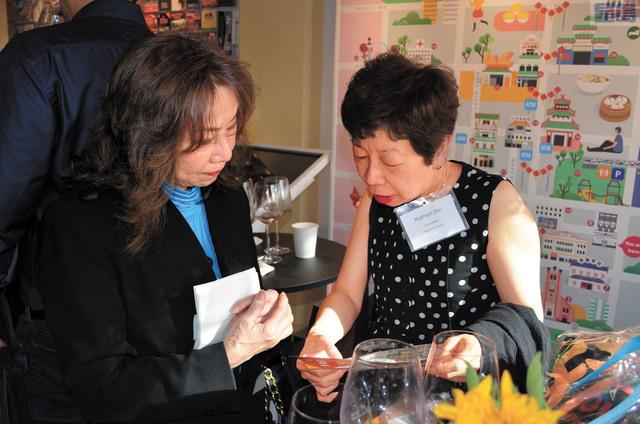 萬豪酒店大堂主管Kathryn Dim(右)向訪客中心工作人員咨詢服務信息。記者劉玉姝攝