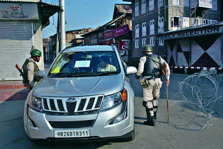 印度軍人周五截查一名前往機場的克什米爾男子。 美聯社