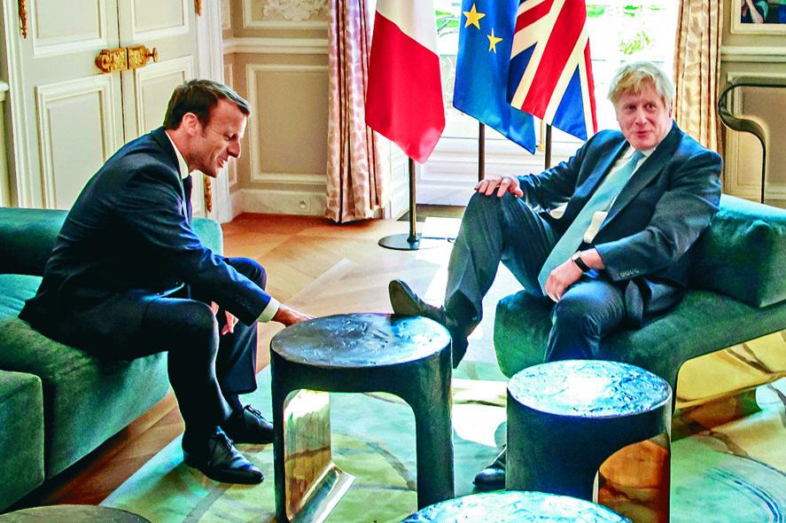 約翰遜(右)周四在愛麗舍宮把腳擱在桌子上,馬克龍坐在他對面。 路透社