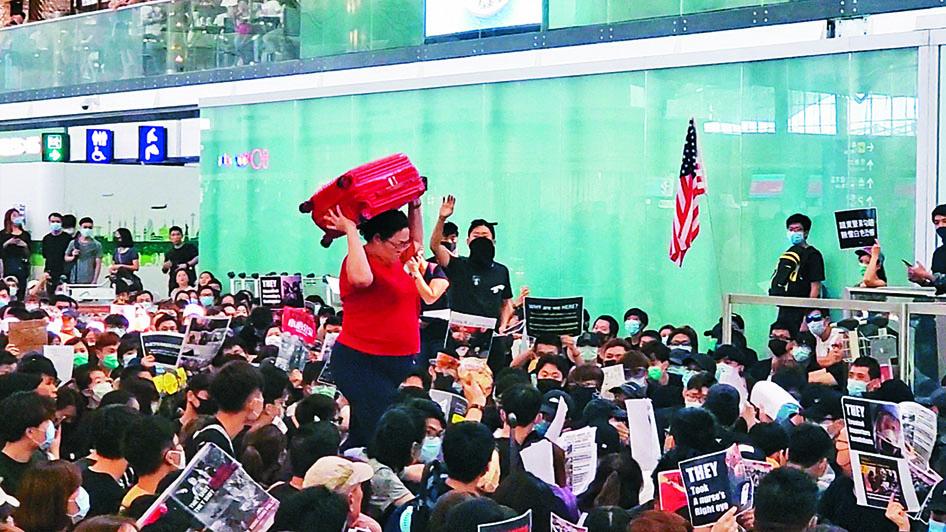 大批示威者堵塞通道,一名旅客千辛萬苦才可進入禁區。