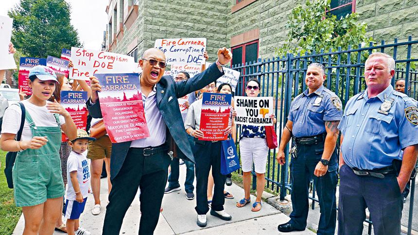 學監進入學校後,華人家長隔著警察,向會場大叫。