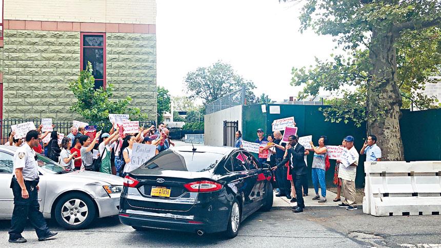 一群華人示威者在紐約市教育總監卡蘭扎的車輛旁抗議。