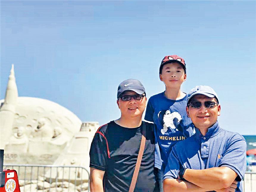 華人遊客在沙雕前留影。李強攝