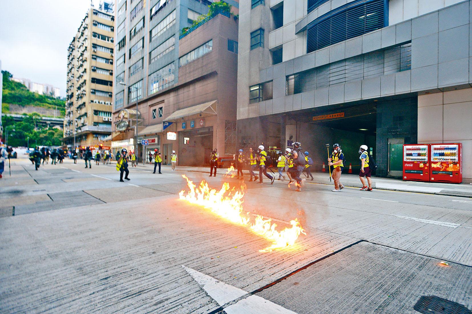 有示威者在長沙灣警署外,點著易燃液體燒出一條火路。梁譽東攝