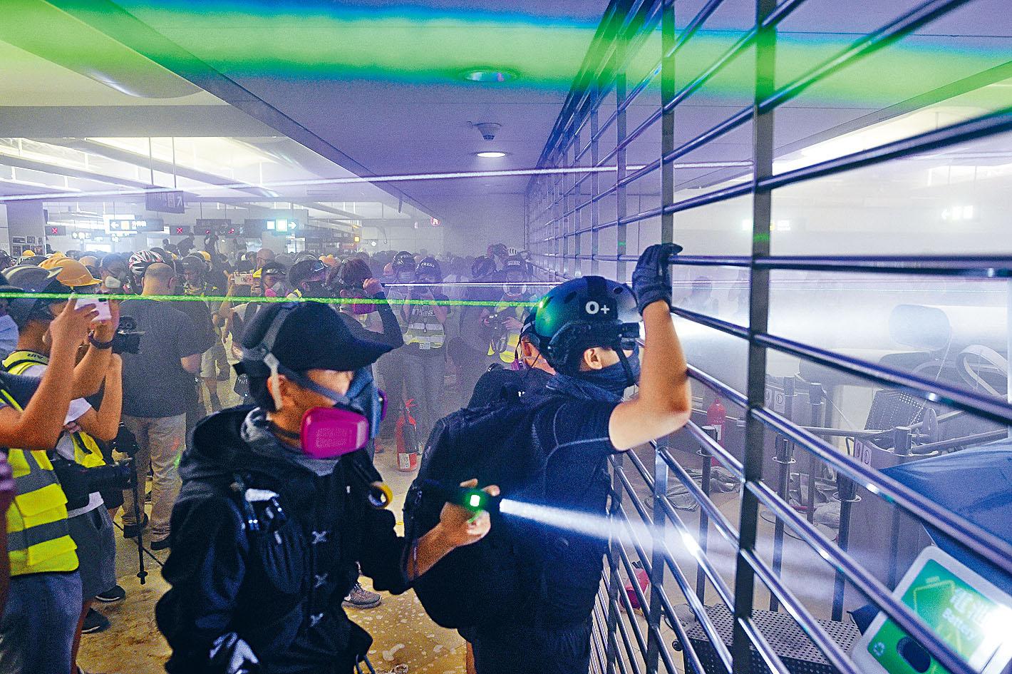 激進示威者在元朗站拉閘,用鐳射筆照射站外的警方防線。蘇正謙攝