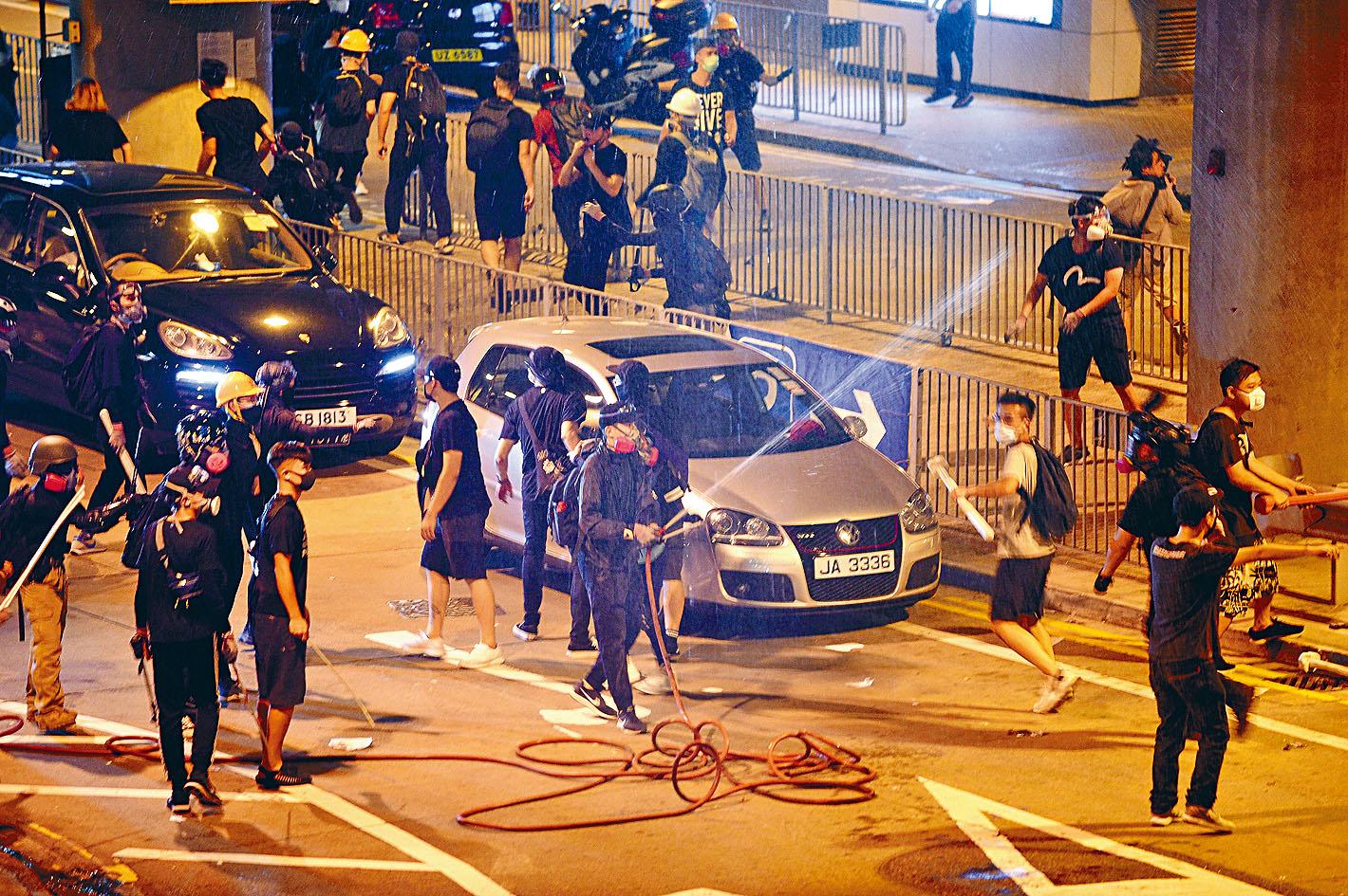 示威者在車站外拉喉射水,圖企阻礙警方清場。蘇正謙攝