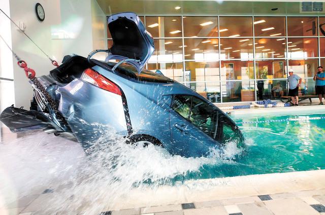 用拖車將汽車拉出游泳池。美聯社