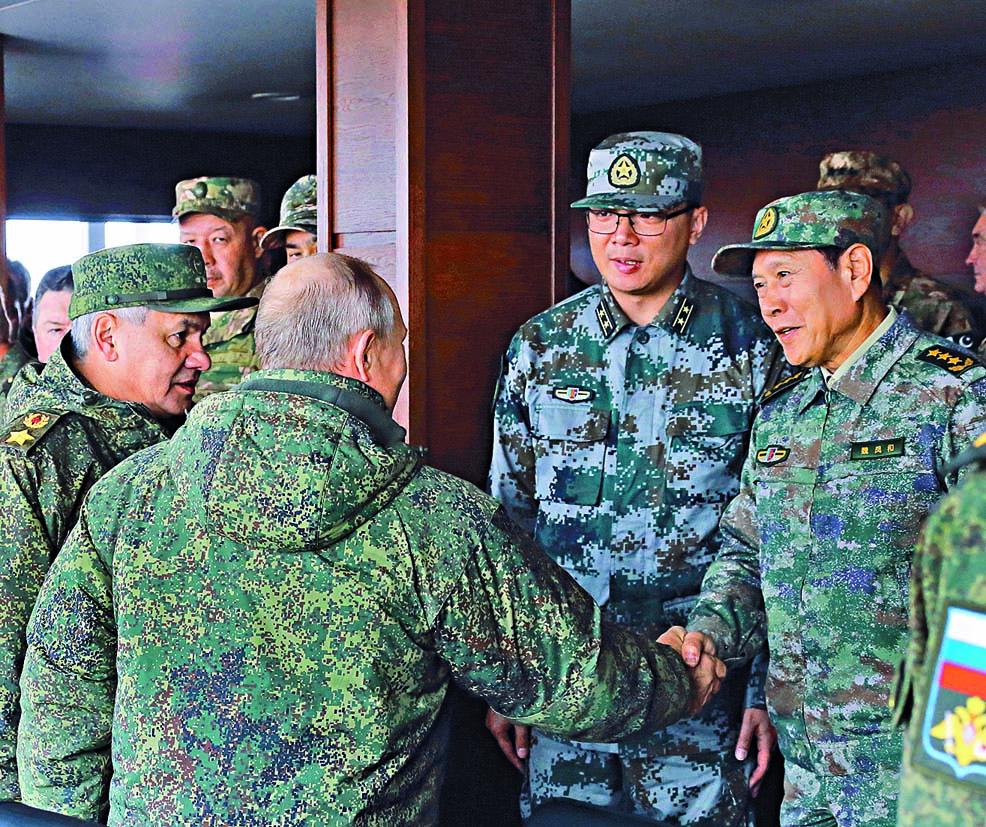 ■中國國防部長魏鳳和與俄羅斯總統 普京在觀摩演習時友好交談。 新華社