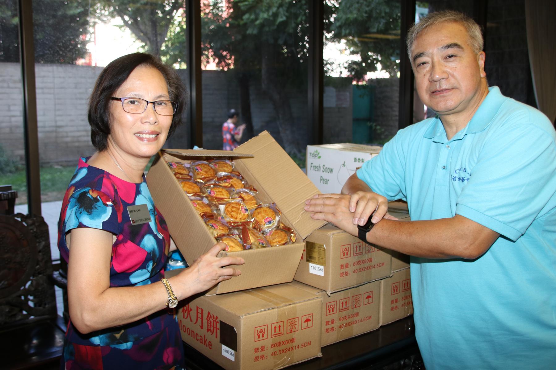 廖美華(左)與劉國賜準備向國泰大廈耆英送上月餅過節。主辦方提供