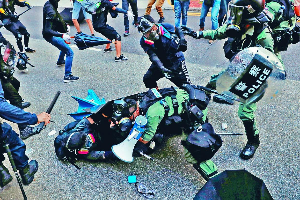 一名示威者圖趁防暴警拉人時,圖從後 搶槍,幸及時遭制止。 路透社