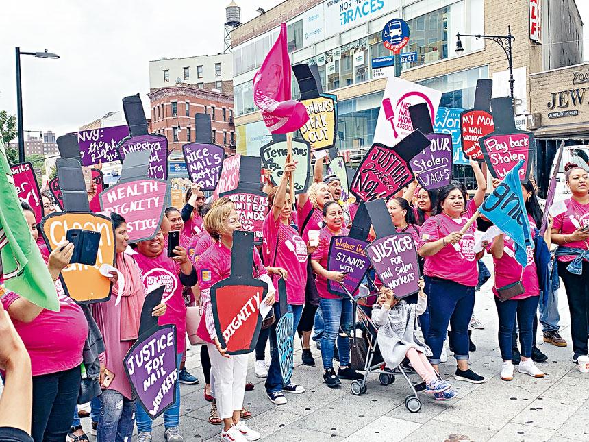 近百名美甲業者手舉標語,呼籲改革美甲業工作環境。