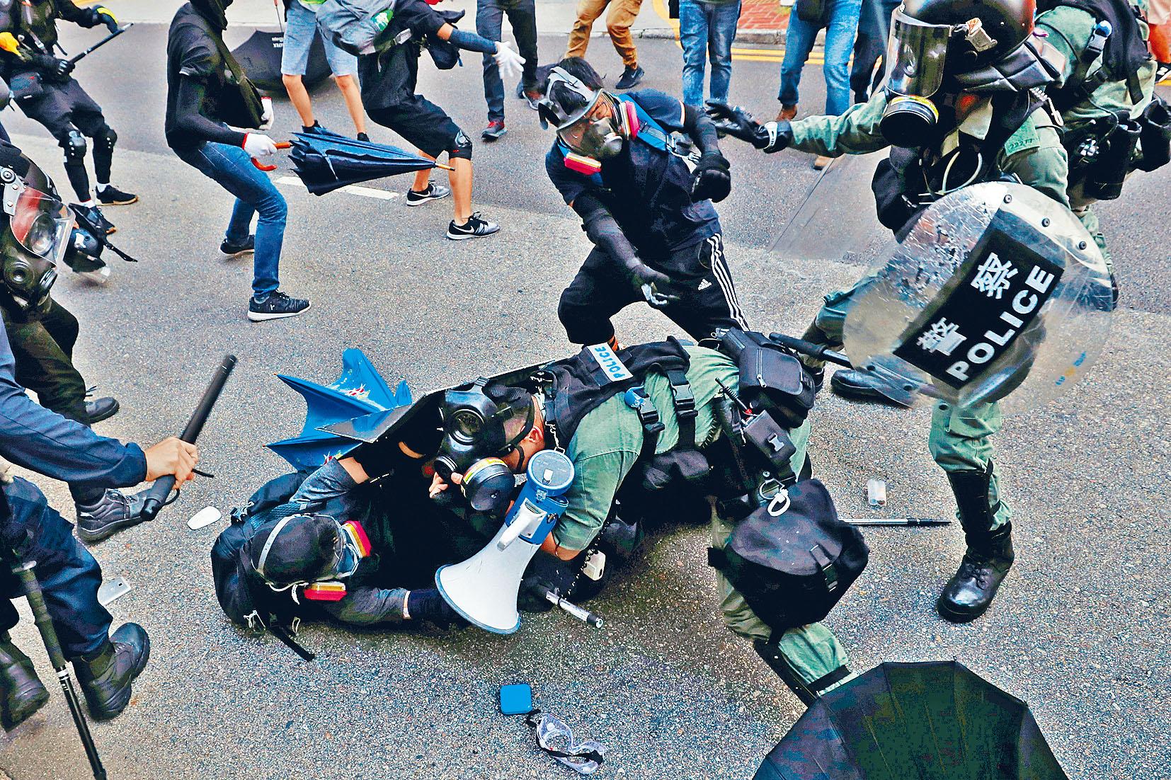 一名示威者圖趁防暴警拉人時,圖從後搶槍(紅圈示),幸及時遭制止。路透社