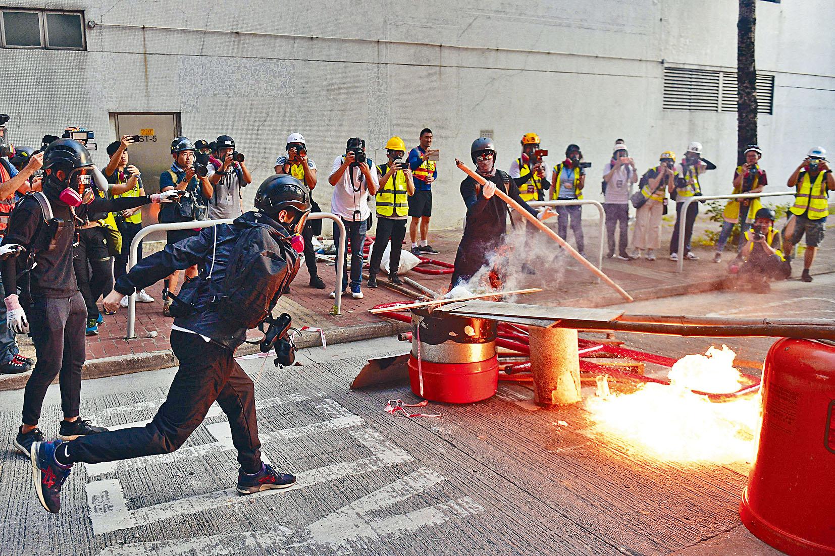 一名激進示威者在馬路焚燒雜物,試圖與警對峙。法新社