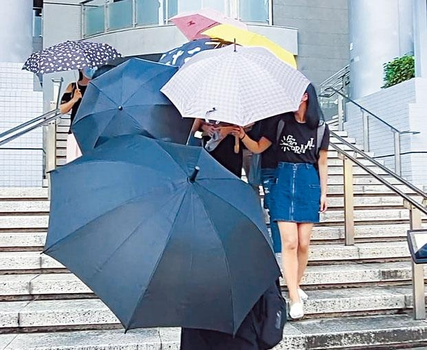 羅樂文在多名親友的雨傘陣掩護下離開法院。