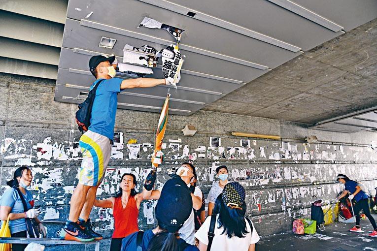 響應「十八區清潔香港運動」的市民四出「清牆」。