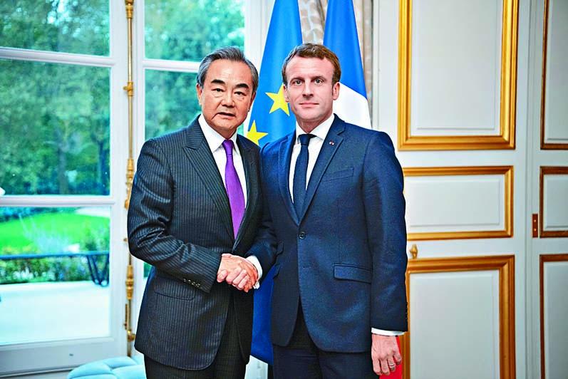 法國總統馬克龍(右)在巴黎會見王毅(左)。