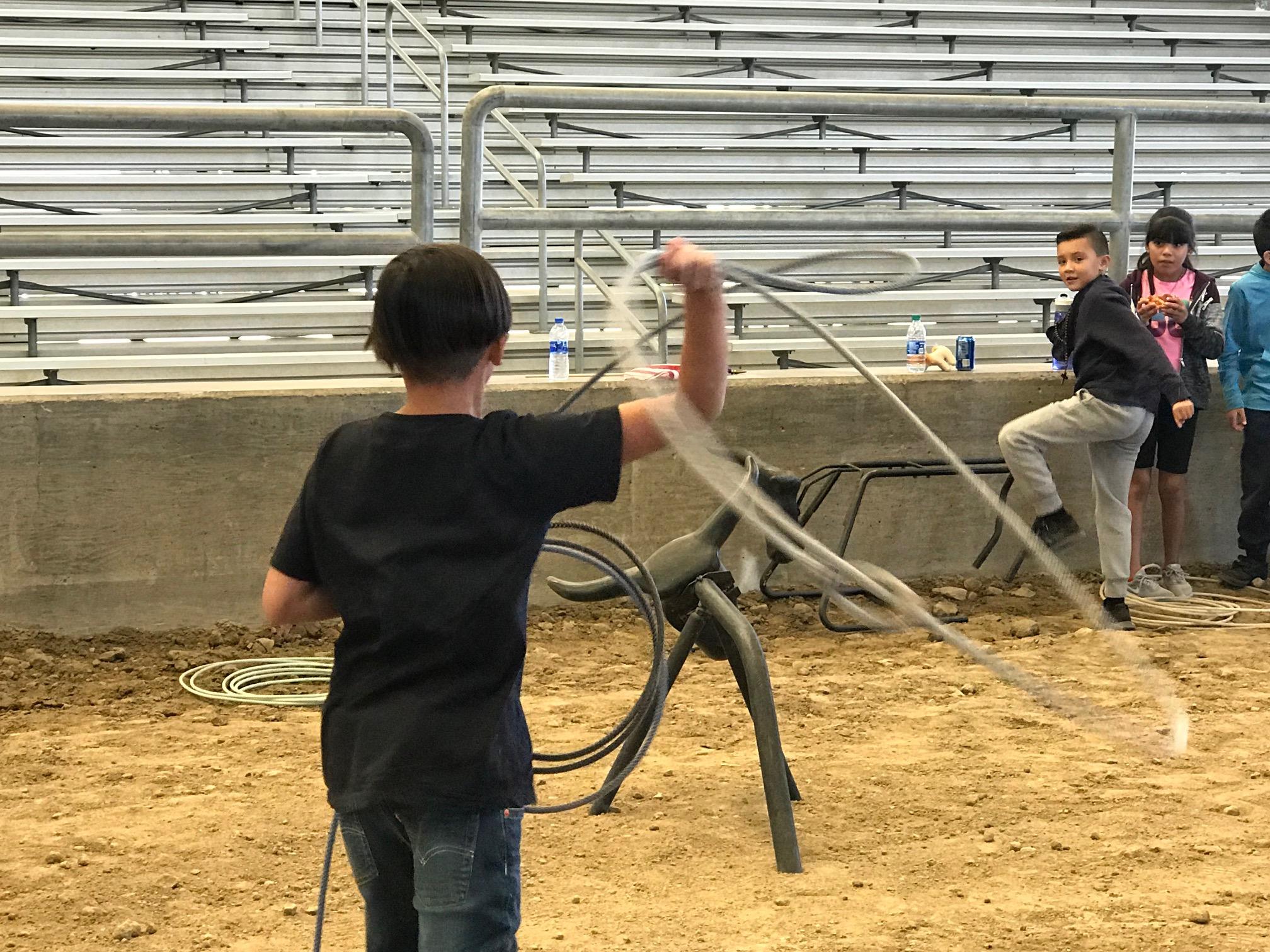 一名學生在牛仔的指導下試圖用繩子套住牛模型的頭。記者林宇婧攝