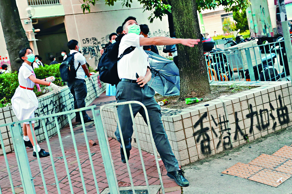 有身穿校服、戴上口罩學生向學校外牆投擲雞蛋等物品。