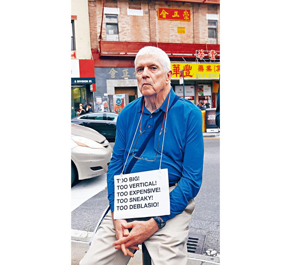 �@位白人老伯,不能久站,坐在路石�演�f,他的�牌�f白了一切。