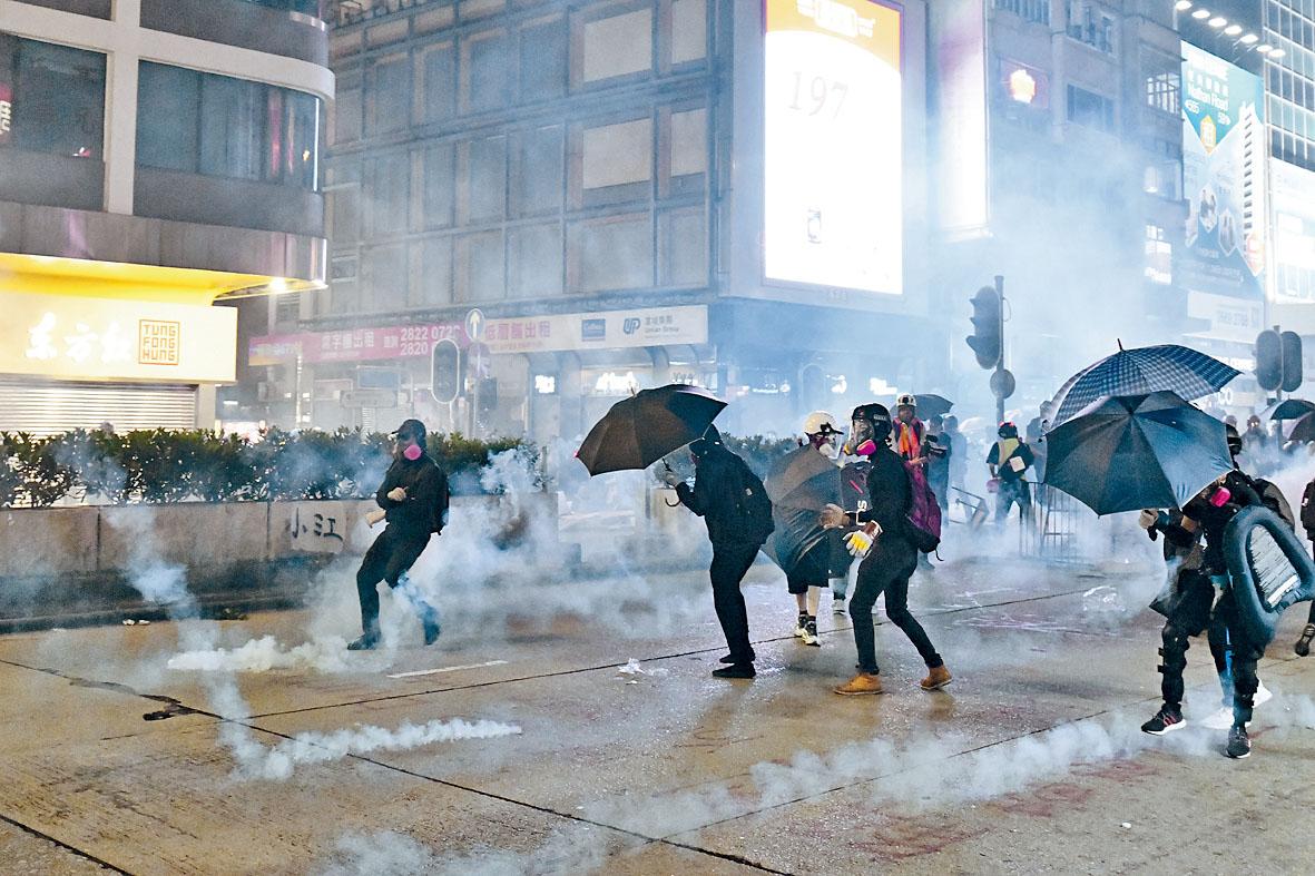 黑衣人利用雨傘遮擋,試圖在催淚煙中突圍。盧江球攝