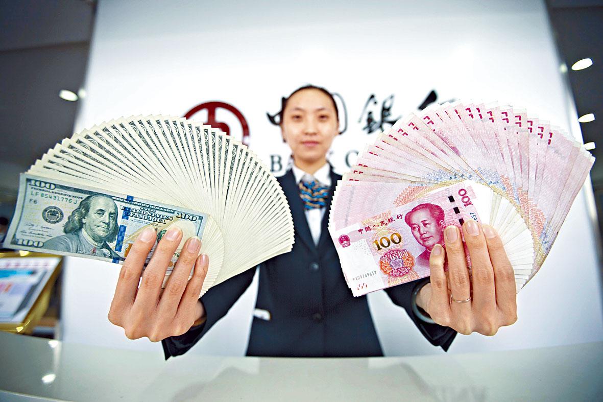 瑞信表示,美中兩國過去一年,強勁創造財富。圖為銀行工作人員手持美元、人民幣。資料圖片