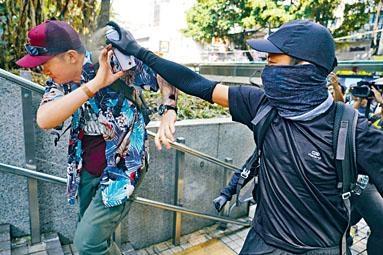 黑衣人在尖沙嘴警署外向撐警內地男子噴漆。
