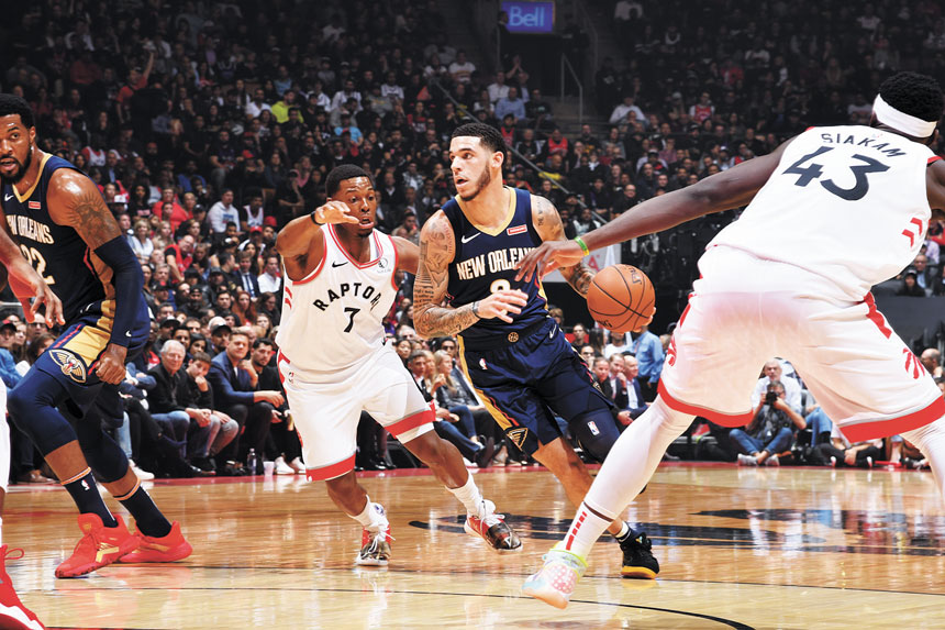 圖為NBA新賽季揭幕戰,鵜鶘隊球員鮑爾(中)突破速龍隊球員的防守帶球組織進攻。Getty Images
