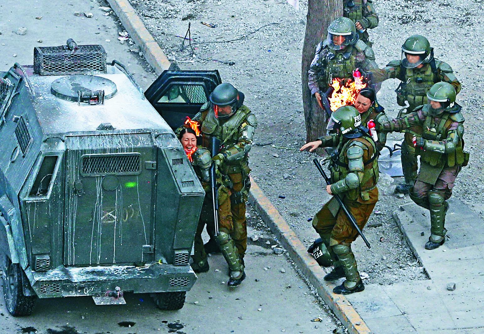 智利首都聖地亞哥周一有反政府示威者向警察擲汽油彈,警員身上起火,同僚跑來幫助撲火。 美聯社