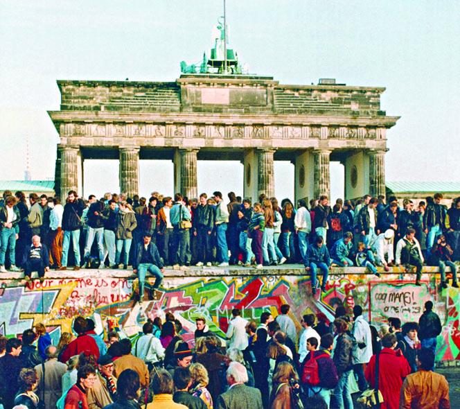 東、西德民眾在一九 八九年十一月十日,站 上勃蘭登堡門前的柏林 圍牆。  資料圖片